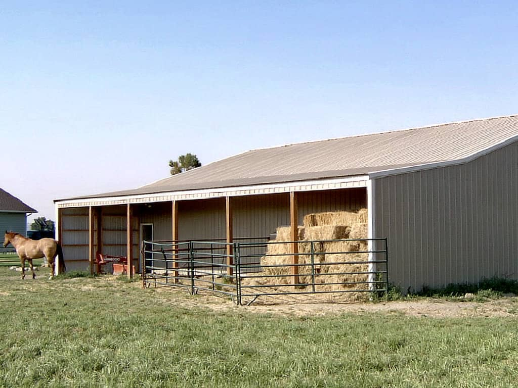 Pole barn with attached lean-to being used for hay storage and animal shelter.