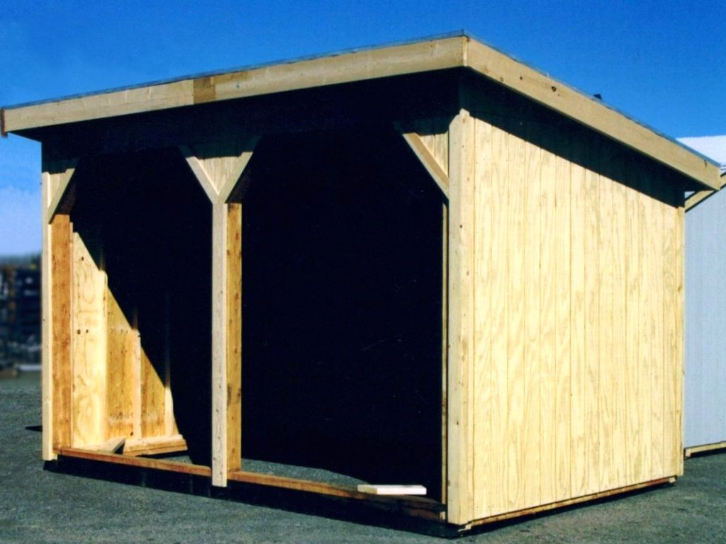 Two-bay wood-sided livestock shelter with a single pitch metal roof.