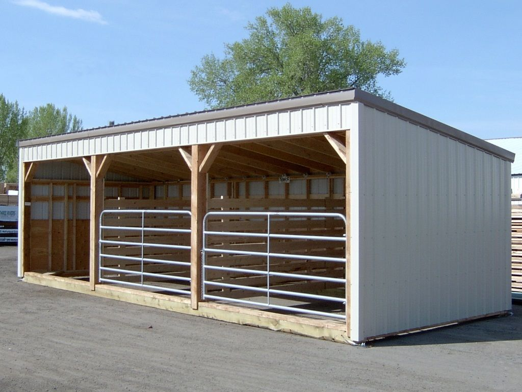 Metal clad livestock shelter with three bays separated with dividers and steel gates on two of the bays.