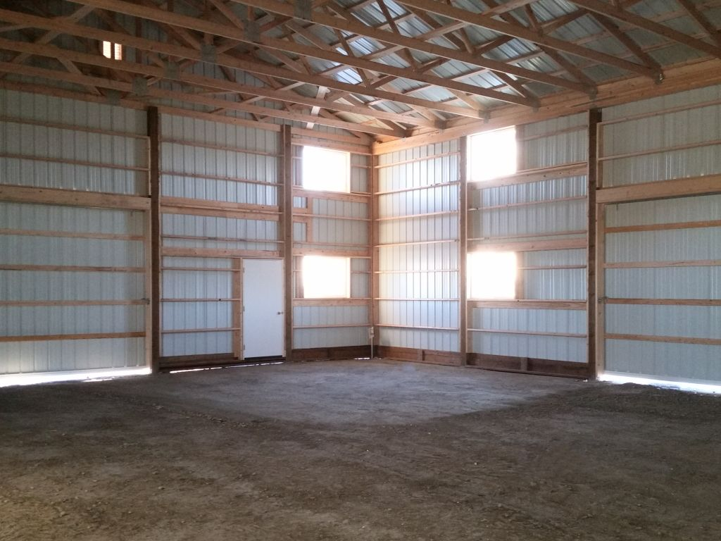 Interior of a pole barn with closed sliding barn doors. Windows let in natural light.
