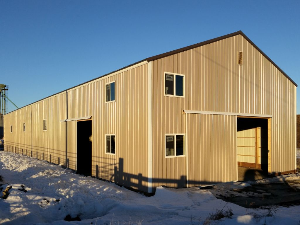 Large, steel-sided, gable-roofed pole barn that has numerous windows and two sliding barn doors.