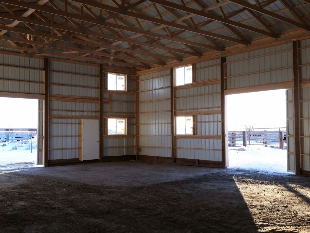 Two open, sliding barn doors let in natural light in a pole barn with turned-girt framing.