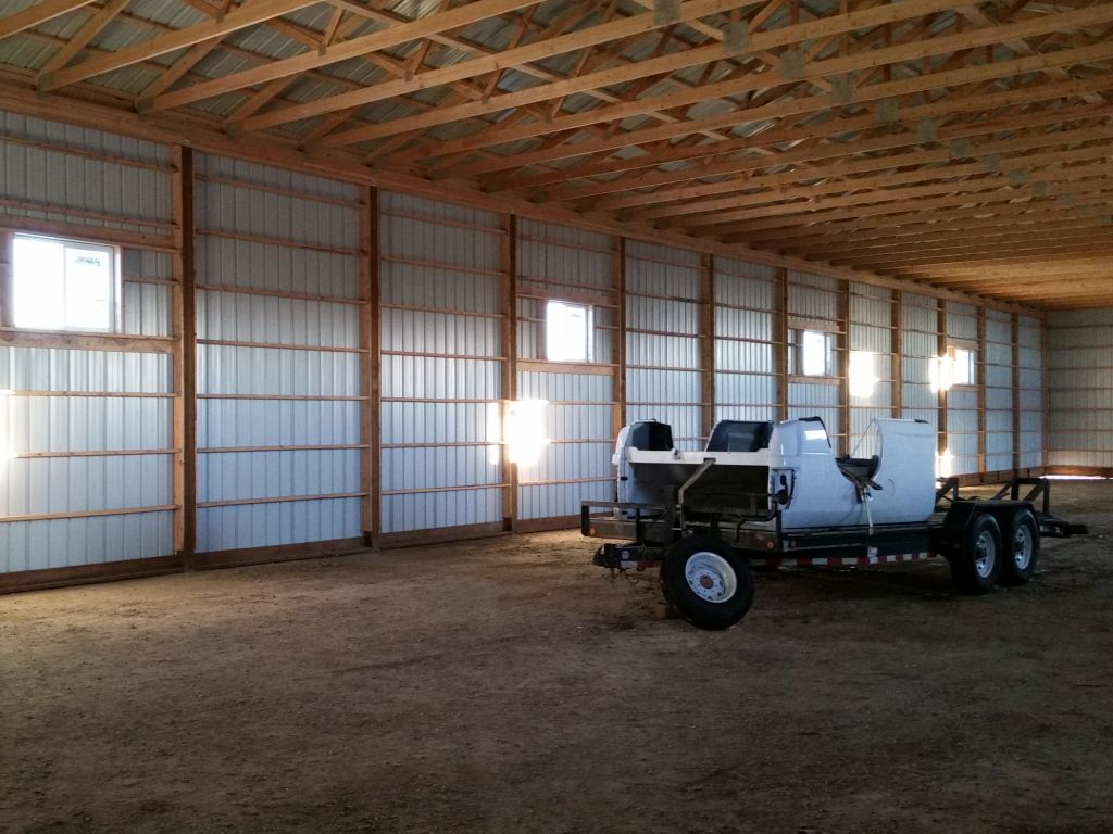 Interior wall of a pole barn showcasing turned-girt framing. A trailer with auto body parts sits inside the building.