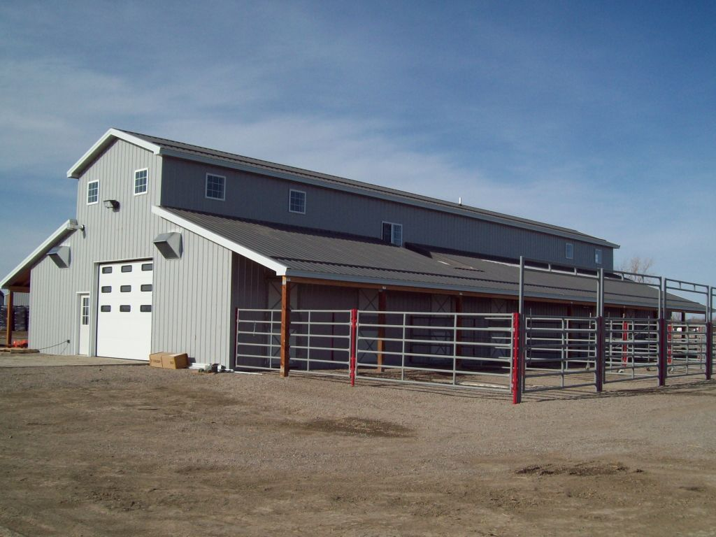 Gray monitor roof, post-frame barn with stall doors leading to small paddocks.