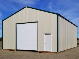 Basic pole barn with tan steel siding and forest green trim and metal roofing. Overhead door and walk door on one end.