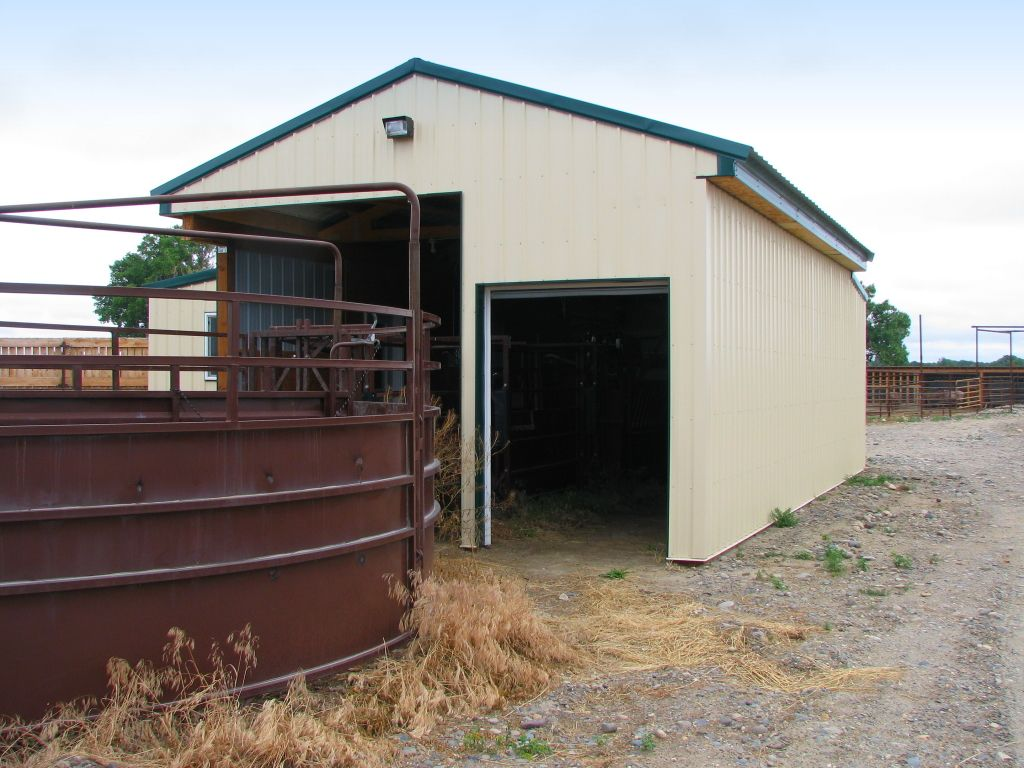 Cream steel siding and a green metal roof on a post-frame building that was built to house livestock equipment.