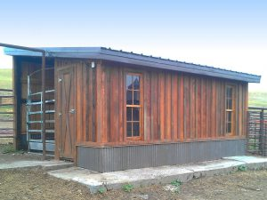 Small outbuilding with a single-pitched steel clad roof and custom board and batten wood siding.