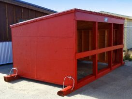 Calf shelter painted red with tow cables on skids.