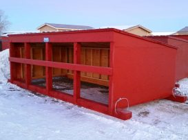 Red calf shelter with metal roof and two cables on the skids.