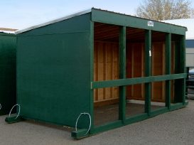 Green painted calf shelter with two cables on skids.