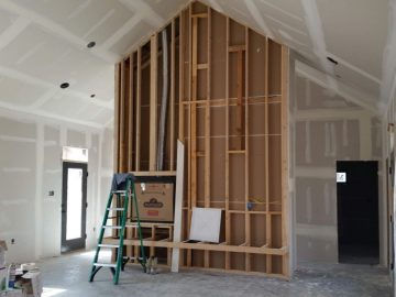 Framed interior wall that is having gas fireplace installed.