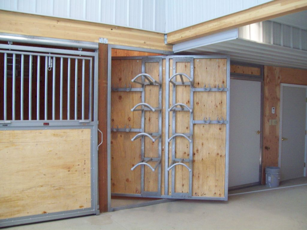 Full view of rotating tack room door that has built in saddle mounts on it.