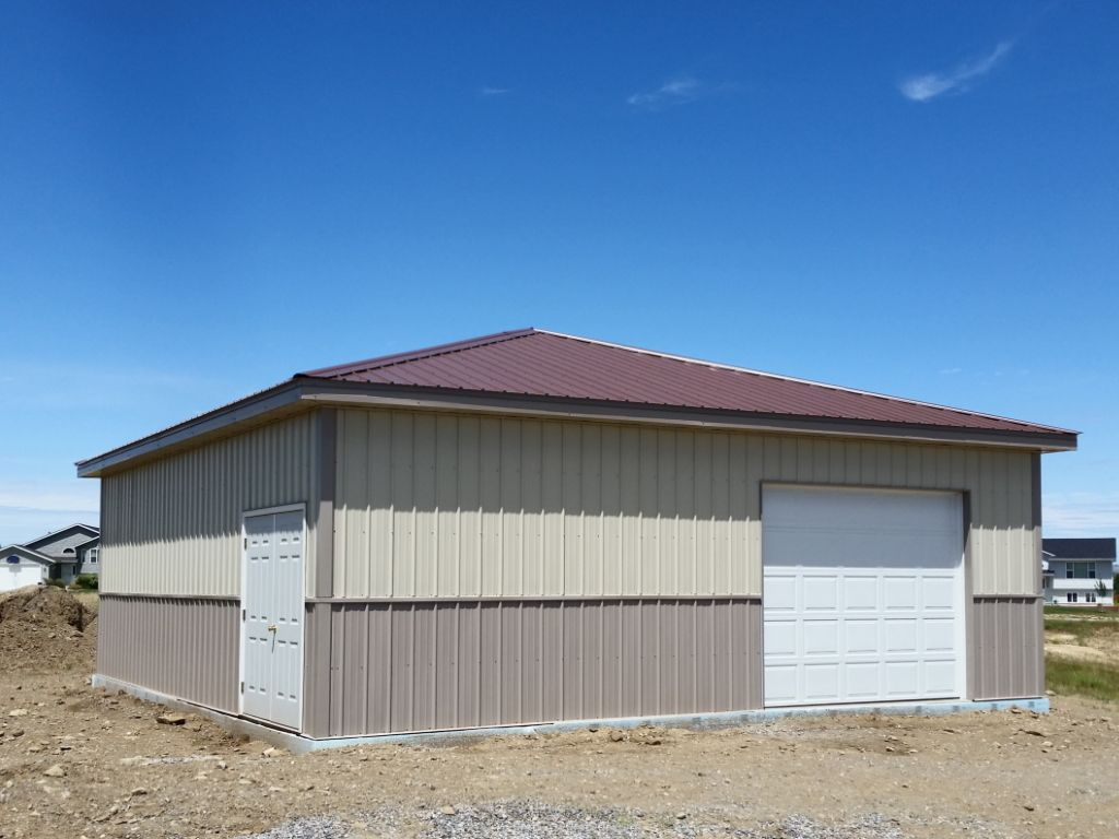 A square garage with a hipped roof. An overhead door is on one side and a french entry door on another.