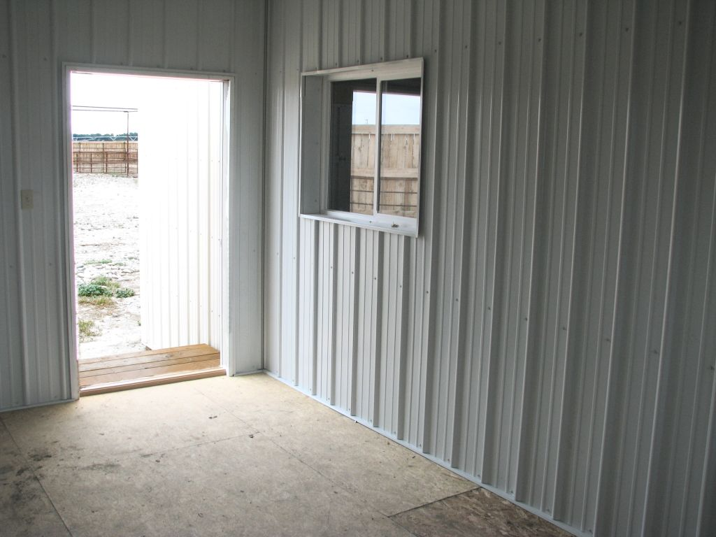 Inside a room looking out an open door. Interior walls are paneled with white steel.