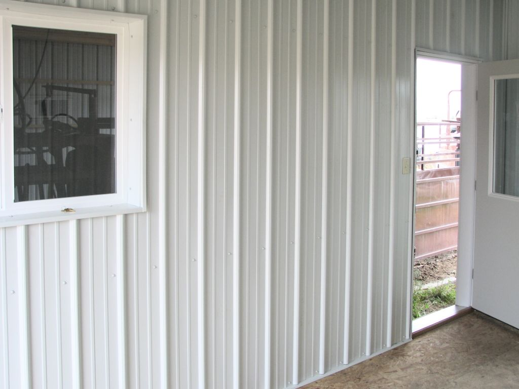 White metal lines the interior wall of a post-frame building.