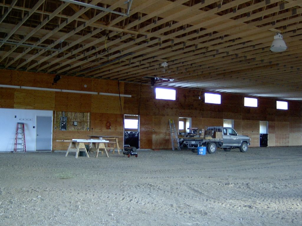 Construction vehicle and equipment inside a riding arena that is being built by S-Bar-S.