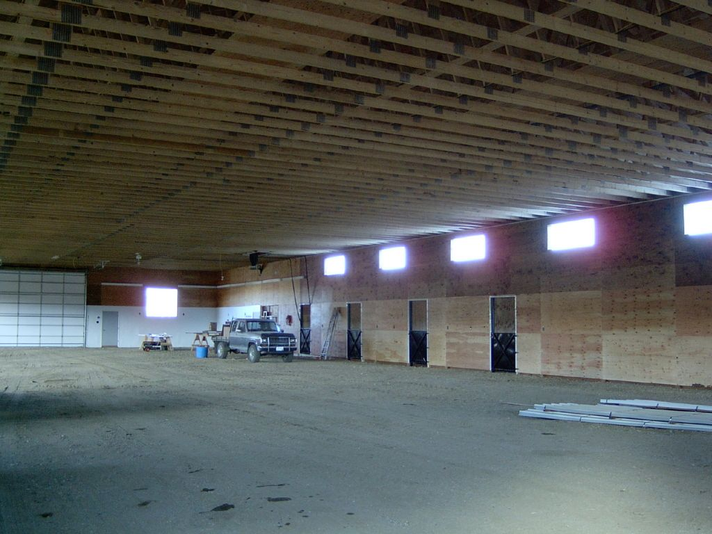 Stall doors line one side of an interior wall in a riding arena that has been lined with plywood.