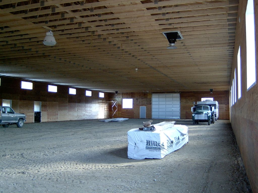 Inside a riding arena that has been lined with plywood. Fiberglass light panel let in natural light.