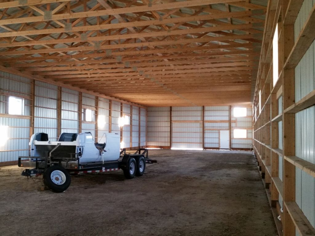 Interior view of a turned-girt post-frame building with trusses visible.