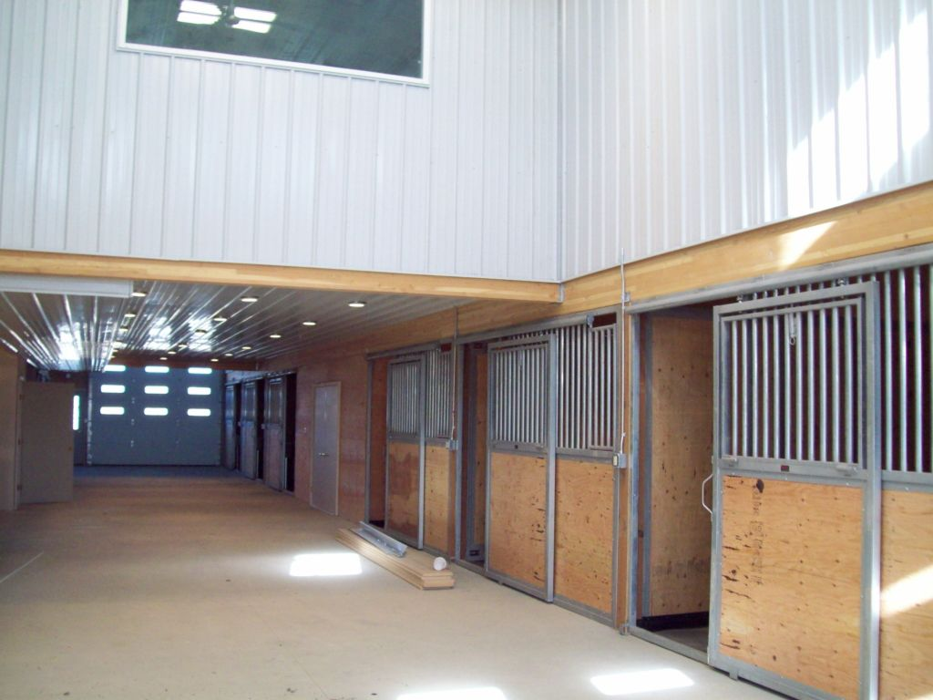 Looking down the barn with metal and wood stalls lining one side and an overhead door on the end.