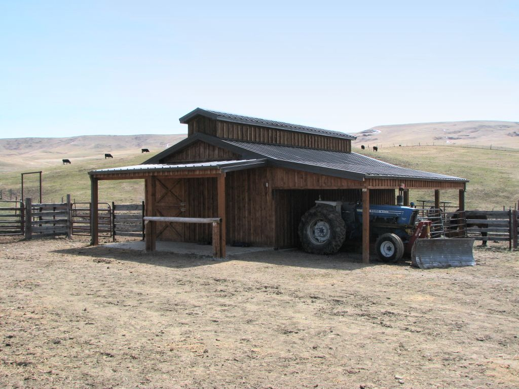 A small post-frame stable with a monitor roof and attached lean-to covered in custom wood siding.