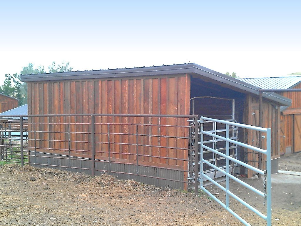 Back side of a small outbuilding with a single-pitched steel clad roof and custom board and batten wood siding.