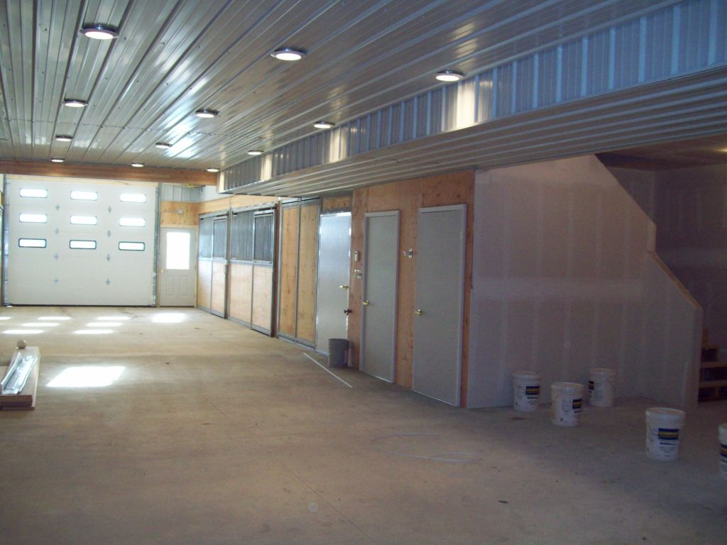 Looking at an overhead door at the end of a barn interior that has recessed lighting.