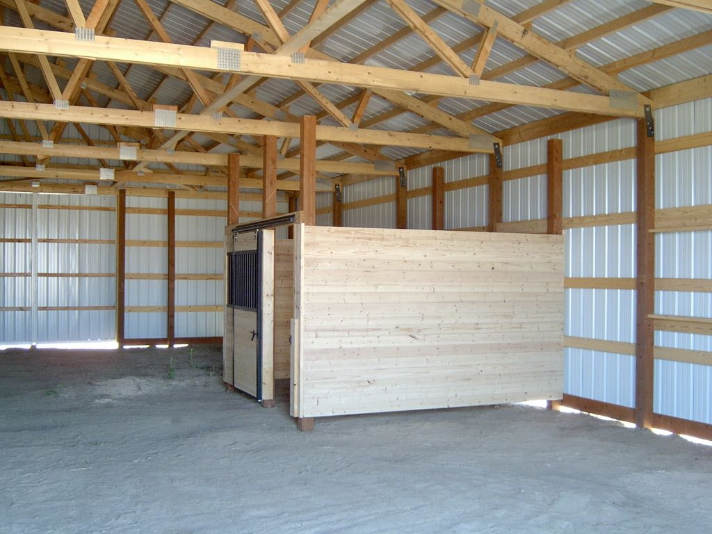 Wooden stall enclosure sits amid a standard built pole barn wall.