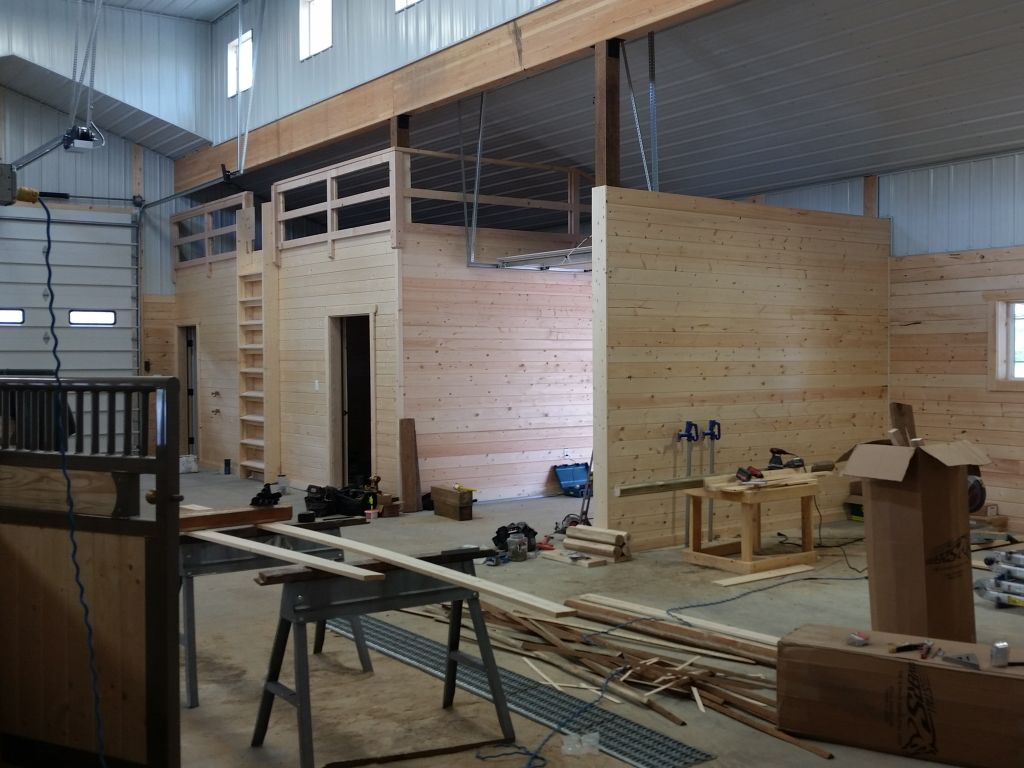 Wooden stable interior in a metal pole barn with construction paraphernalia in the foreground.