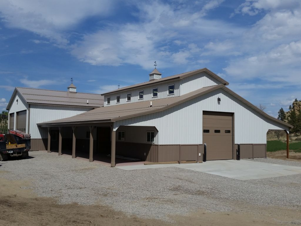 White and brown steel pole barn with varied rooflines accented by cupolas and weathervanes built by S-Bar-S.