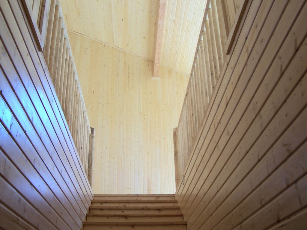 Looking up a staircase with tongue and groove wood paneling and wooden railing to a room paneled in the same wood.