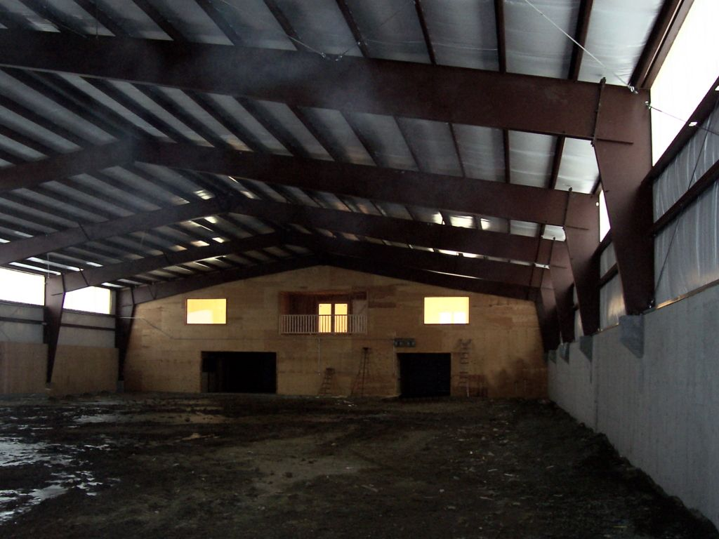 Open interior of a riding arena constructed with red iron trusses.