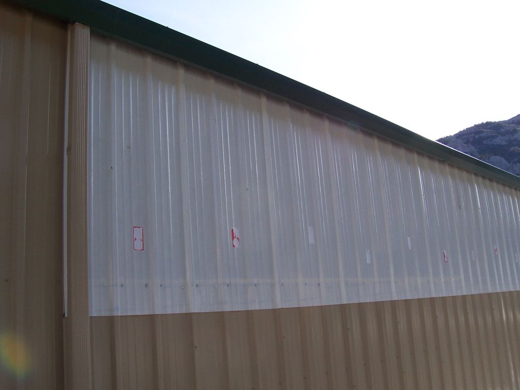 Close-up detail of fiberglass light panels added to a tan metal-sided post-frame building.
