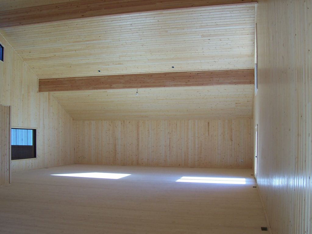 Riding arena observation room paneled in rustic wood and having exposed glu-lam beams.