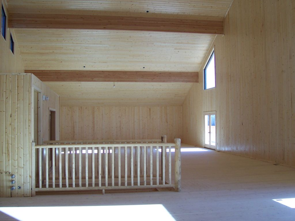 Rustic wood paneling surrounds a great room that is lit with natural light from French doors and picture windows.