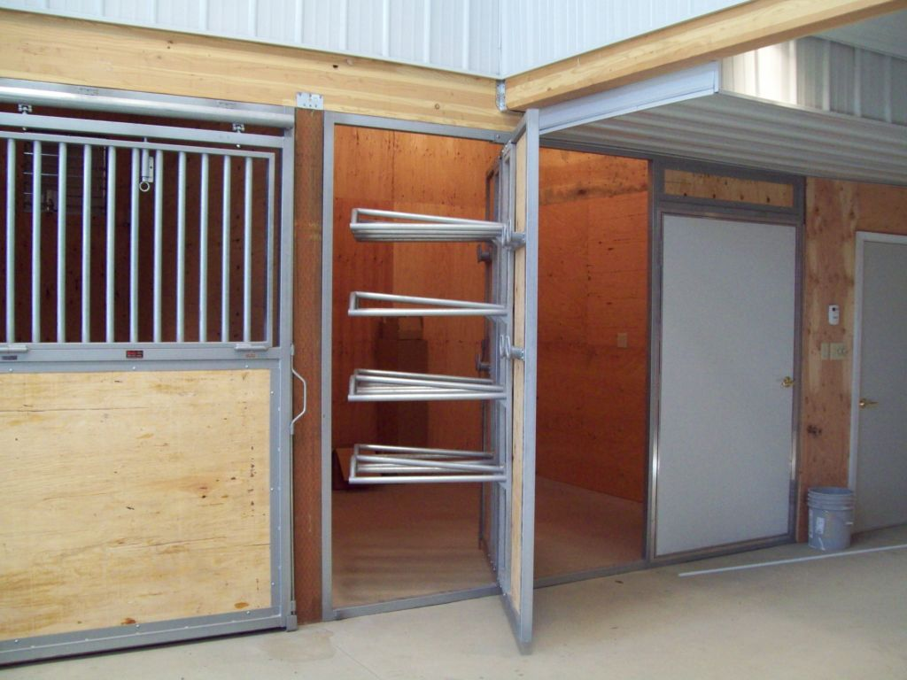 Tack room with rotating door that has built in saddle holders on one side.