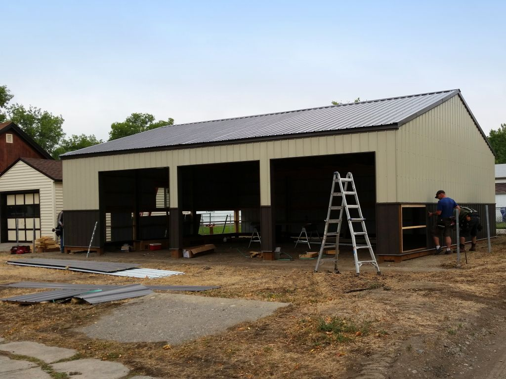 Men attaching brown steel wainscot to a three bay garage that is being built.