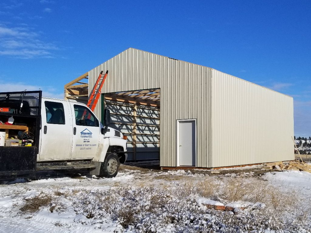 Pole barn under construction with tan steel siding being installed. S-Bar-S work truck parked in front.
