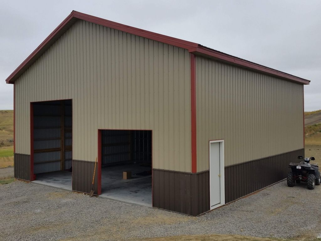 Pole barn shop with tan siding, brown wainscot and rust-red trim & roof. Overhead doors not installed yet.